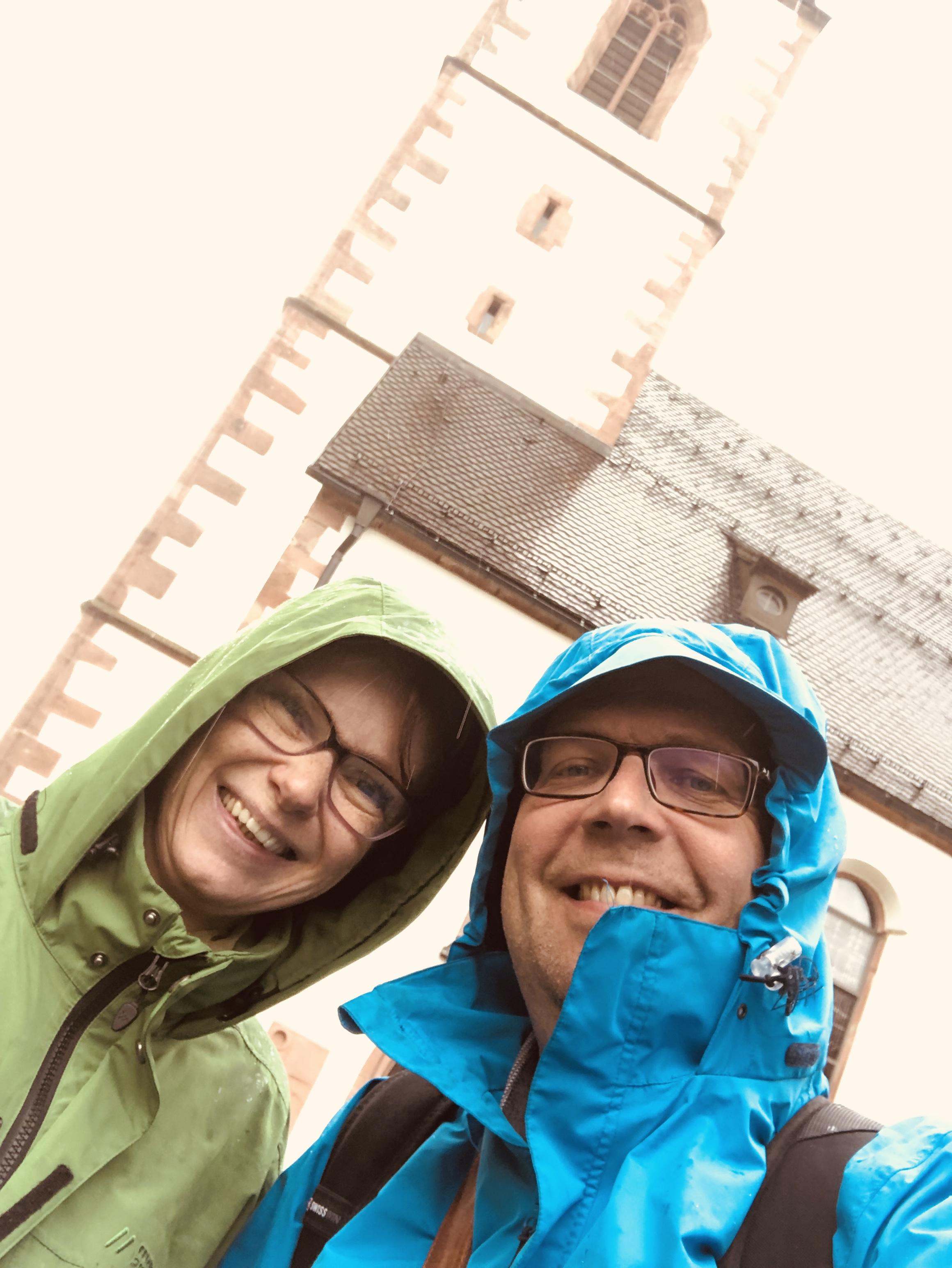 Die Kirche in Wolfach. Katja und Matthias stehen lachend davor.